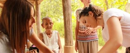 A Cambodian woman is examined by Projects Abroad medical interns during a community outreach.